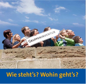 Eine Gruppe Menschen, die gemeinsam ein Schild mit der Aufschrift Gruppeninventur tragen. Darunter steht: Wie steht's? Wohin geht's?