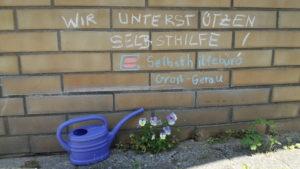Auf einer Mauer ist mit Kreide geschrieben: Wir unterstützen Selbsthilfe Selbsthilfebüro Groß-Gerau. Vor der Mauer steht eine Gießkanne. Blumen wachsen vor der Mauer
