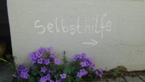 Eine Mauer, davor lila Farben Blumen. Auf der Mauer steht mit Kreide geschrieben das Wort Selbsthilfe darunter ein Pfeil, der nach rechts zeigt