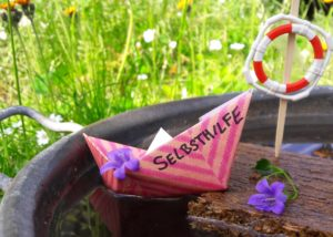 Ein selbstgebasteltes Papierschiffchen mit der Aufschrift Selbsthilfe in einem Wasserbehälter. Daneben ein Stück Treibholz mit Rettungsring.
