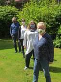 Vier Menschen tragen eine Maske und stehen mit Abstand hintereinander auf einer Wiese