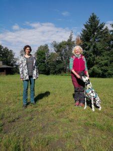Zwei Menschen stehen mit einem Hund auf einer Wiese